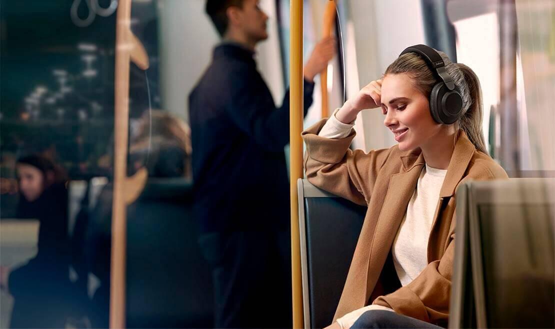 Woman using Jabra Elite 85h wireless headphones in public transportation